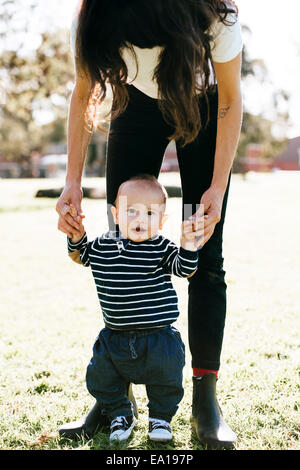 Woman supporting son in first steps - Stock Photo