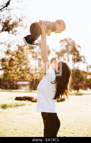Mother swinging son in air - Stock Photo