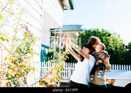 Woman taking family selfie at front of house - Stock Photo