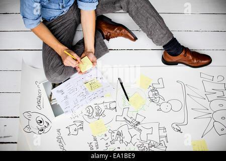 Graphic designer producing creative ideas on floor - Stock Photo