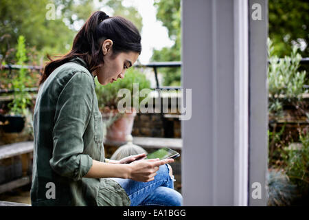 Woman using digital tablet by terrace - Stock Photo