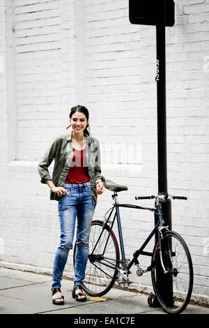 Woman standing beside bicycle - Stock Photo