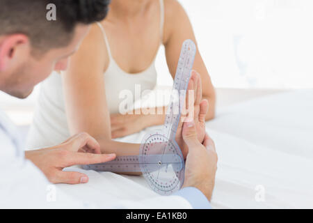 Physiotherapist examining patients wrist - Stock Photo