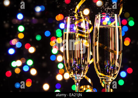 Glasses of champagne on black background with blur colored spot lights. Concept of celebration - Stock Photo