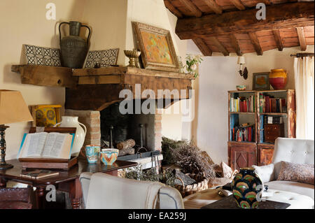 Large timber and stone fireplace in living room with ceiling beams and distressed cabinet - Stock Photo