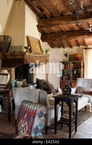 Chair upholstered in Turkish carpet fabric in living room with orginal ceiling beams and large stone fireplace - Stock Photo