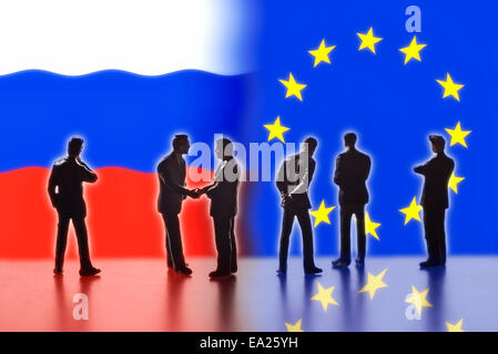 Model figures symbolizing politicians are facing the flags of Russia and the EU. Two of them shake hands. - Stock Photo
