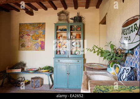 Blue dresser full of brightly coloured crockery and jugs in rustic room with artwork and vintage enamel sign - Stock Photo
