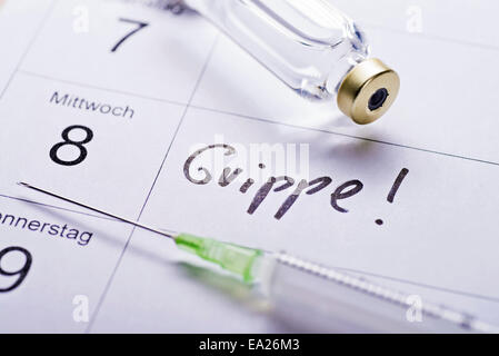 Syringe and vaccine on a calendar with the date for influenza vaccination. - Stock Photo
