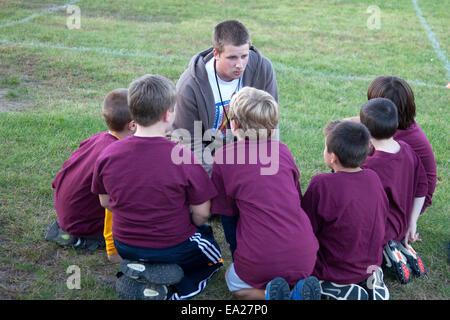 Teen coach instructing his boys soccer team age 8. St Paul Minnesota MN USA - Stock Photo
