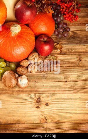 Autumn concept shot from top. Mix of pumpkins, fruit and vegetable on wooden table. - Stock Photo
