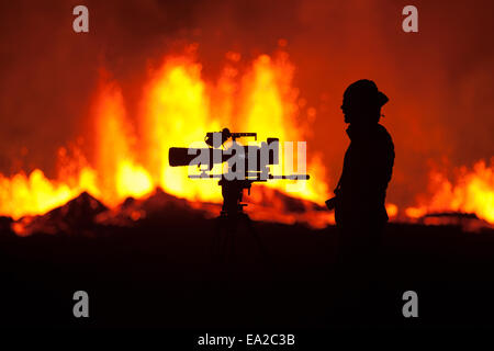 cameraman silhouetted against the iceland eruption - Stock Photo