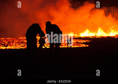 film crew working in front of lava flow - Stock Photo