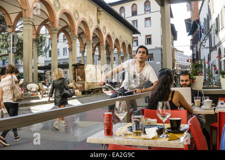 young Italian man on bicycle stops to chat with friends at sidewalk cafe opposite relocated Renaissance loggia & - Stock Photo