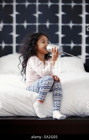 A young girl is playing with a can and string communication device; San Francisco, California, United States of - Stock Photo