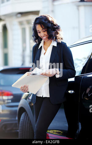 A businesswoman leaning against her car looking at some files; San Francisco, California, United States of America - Stock Photo