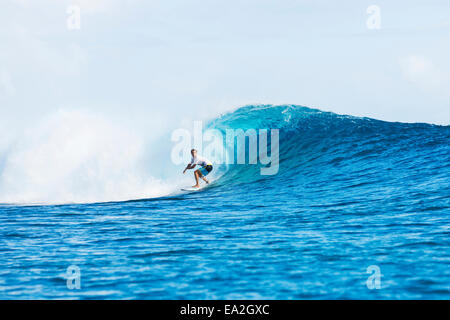 Surfer riding perfect waves in the South Pacific; Tahiti, French Polynesia - Stock Photo