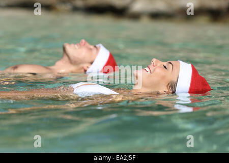Couple swimming on a tropical beach on christmas holidays in a clean transparent sea water - Stock Photo