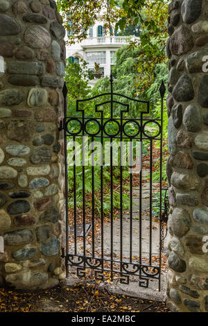Steel gate with stone posts leading into garden. - Stock Photo