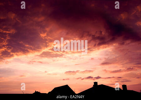 Sunset red sky with dark dramatic clouds over houses. - Stock Photo