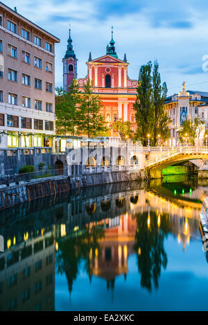 Ljubljana triple bridge and Franciscan Church of the Annunciation reflected in Ljubljanica River at night, Ljubljana, - Stock Photo