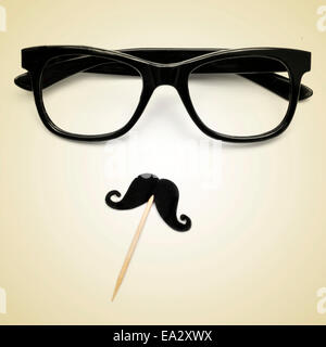 eyeglasses and a moustache depicting a gentleman or a hipster guy on a beige background, with a retro effect - Stock Photo