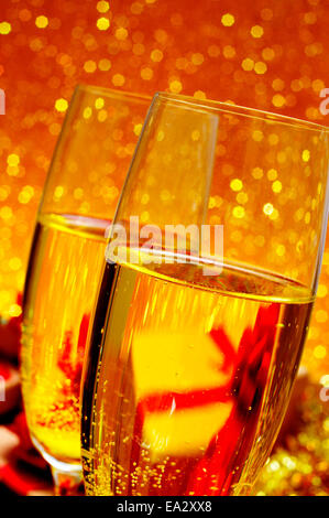 closeup of two glasses with champagne on a festive and shiny golden background - Stock Photo