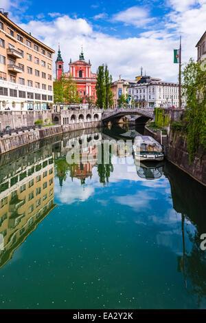 Ljubljana triple bridge and Franciscan Church of the Annunciation reflected in Ljubljanica River, Ljubljana, Slovenia - Stock Photo