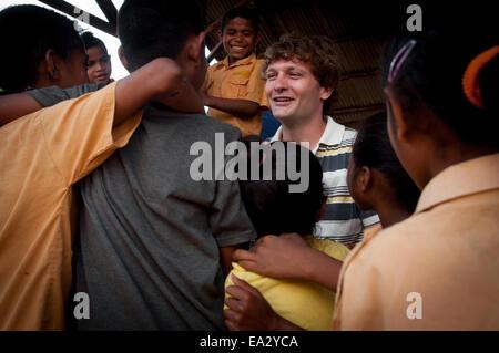 A western man talking to local children at Labalimut village, Lembata Island, Indonesia. - Stock Photo