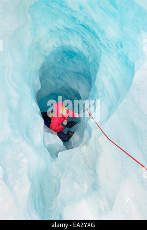Rock climber moving up ice cave, Fox Glacier, South Island, New Zealand, Pacific - Stock Photo