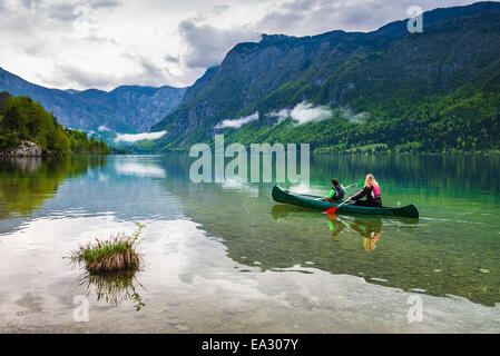 Mother and son canoeing on Lake Bohinj, Triglav National Park, Julian Alps, Slovenia, Europe - Stock Photo