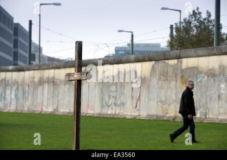 Berlin, Germany. 05th Nov, 2014. A man walks past a wooden cross at the Bernauer Strasse Berlin Wall Monument in - Stock Photo
