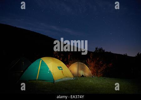 Illuminated yellow camping tent under stars at night - Stock Photo
