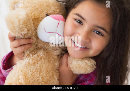 Young smiling girl with stuffed toy - Stock Photo