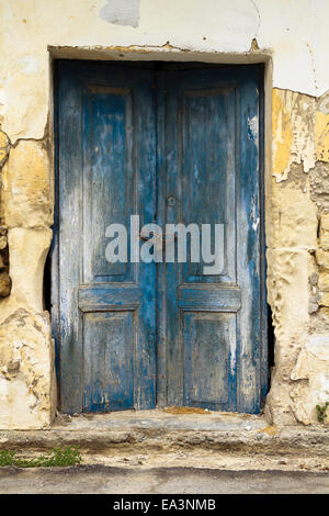 Old ruin with blue double wooden locked doors as building entrance - Stock Photo