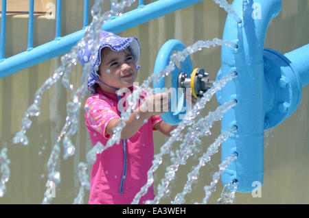 Child (girl age 04) play with water fountain in water park.Concept photo with copy space - Stock Photo