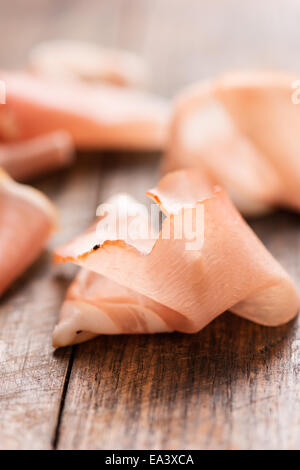 Cured ham on wooden background vertical - Stock Photo
