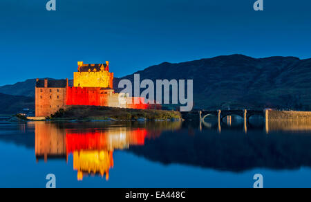 EILEAN DONAN CASTLE SCOTLAND AND BRIDGE WITH EVENING  RED LIGHT REFLECTIONS FOR ARMISTICE DAY NOVEMBER 11 2014 - Stock Photo