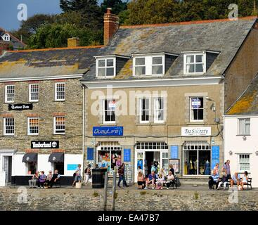 Tourists enjoying the morning sun on the quayside in Padstow Cornwall England uk - Stock Photo