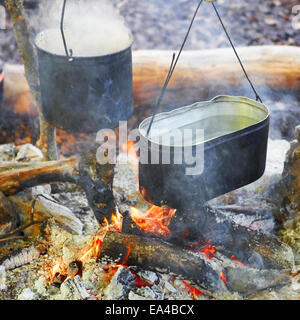 Boiling water in two pots above the fire. - Stock Photo