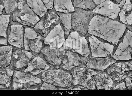 Texture of old vertical stone wall in black and white - Stock Photo