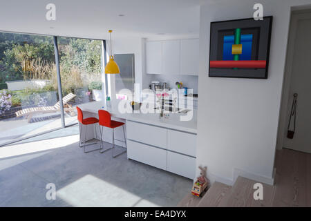 Open plan kitchen with orange bar stools and view to garden in London home, UK. - Stock Photo
