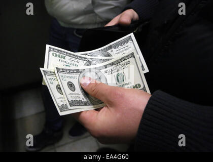 Moscow, Russia. 6th Nov, 2014. A customer of a currency exchange office holds US Dollar banknotes. Credit:  Pavel - Stock Photo