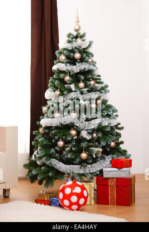 Decorated artificial Christmas tree in room,  presents under - Stock Photo