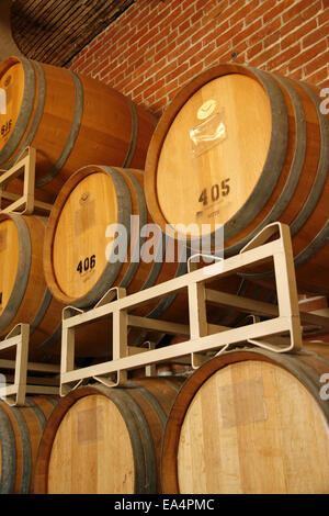 Wine barrels stacked in cellar area of winery - Stock Photo