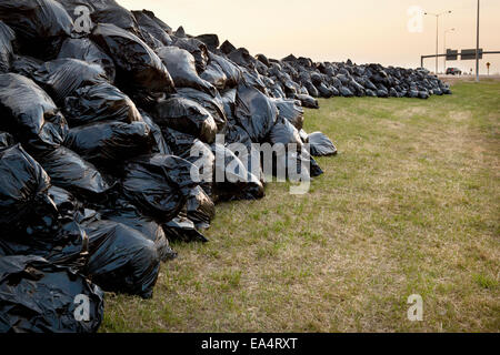 Hundreds of full black garbage bags along the Anthony Henday Highway; Edmonton, Alberta, Canada - Stock Photo