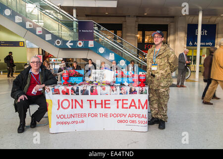 Volunteers selling poppies for the Poppy Appeal for Remembrance Day at a stall in Waterloo Station concourse, London - Stock Photo