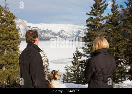 Couple with a dog looking from viewpoint at Lake Minnewanka; Banff, Alberta, Canada - Stock Photo