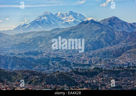 The mountain Illimani rises above the skyline of La Paz; La Paz, Bolivia - Stock Photo