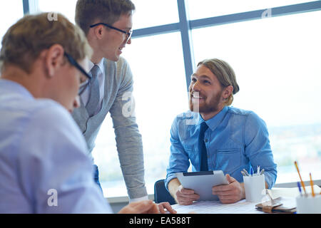 Confident businessmen sharing ideas at meeting - Stock Photo
